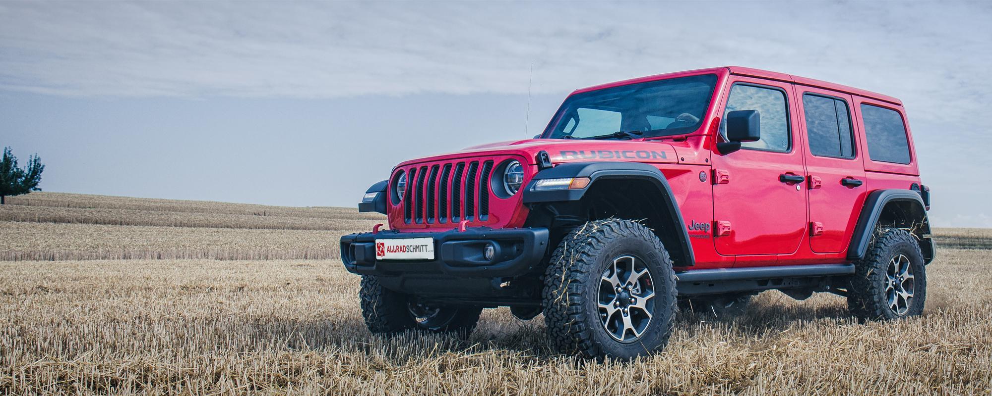 Roter Jeep Wrangler JL auf Feld im Sommer